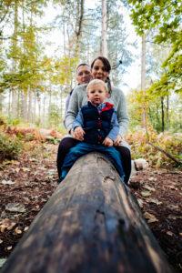 Mum, Dad and Son sitting on log